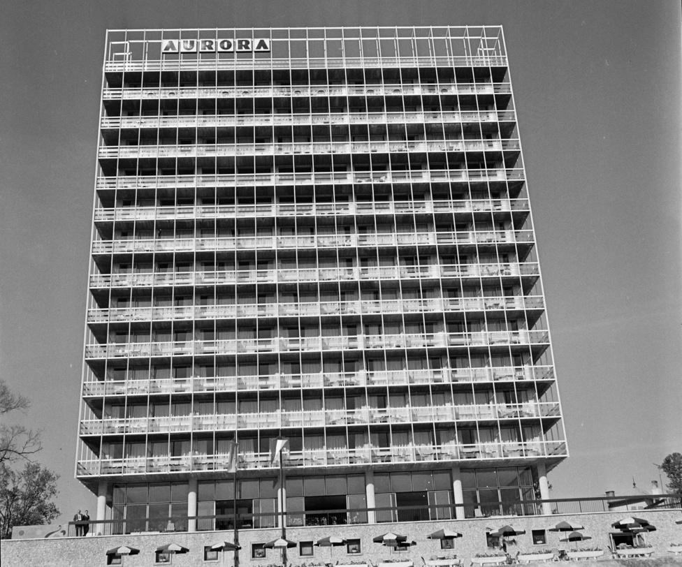 A balatoni nyaralás fellendülése már a 40-es években elkezdődött a szakszervezeti üdültetés beindulásával. Persze az igazi bumm itt is csak a 60-as évekkel jött el. akkor több nívós szálloda is épült a környéken: a Marina, a Helikon, vagy épp ez, az Auróra Almádiban. Ma már gyakorlatilag nincs igazán kiemelkedő minőségű balatoni szálloda ilyen kapacitással.