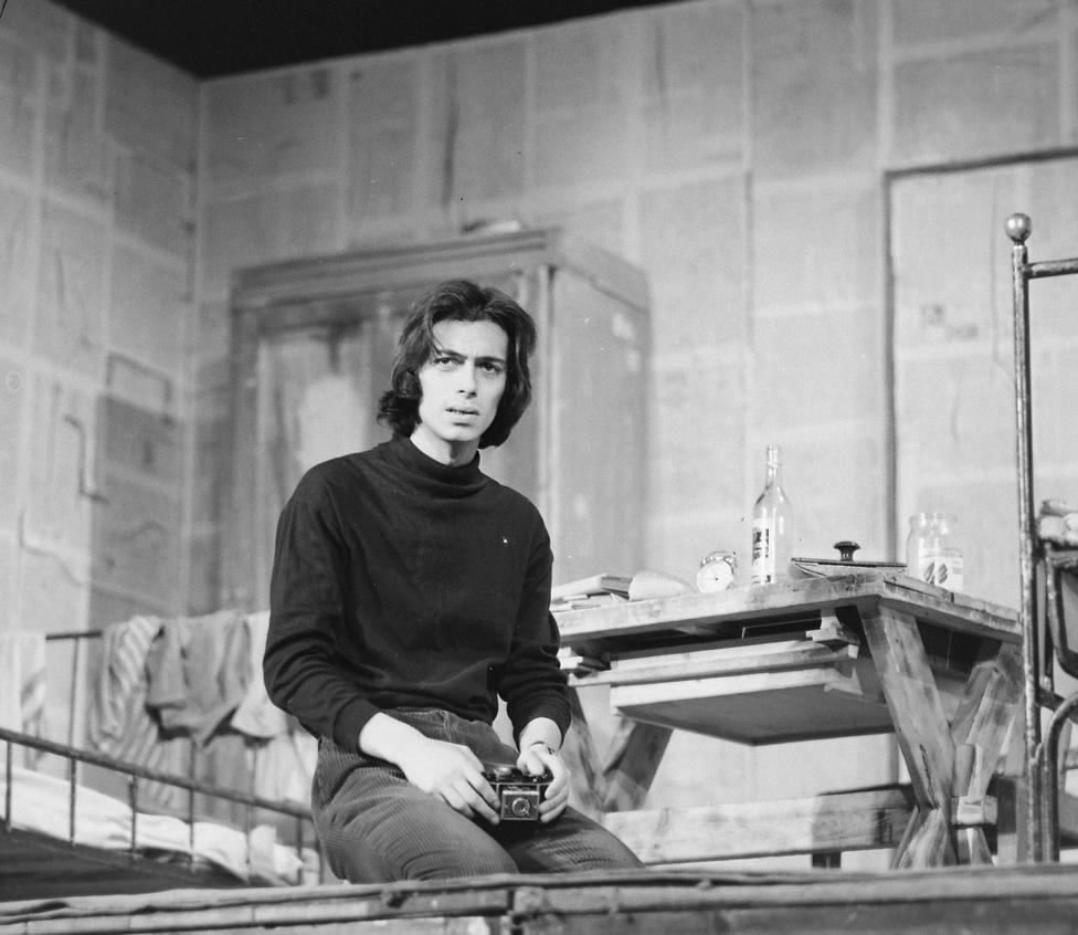 """1972: Varga Károly Oláh János Kenyérpusztítók című darabjában.                         Az 1971/72-es évadban mutatták be Oláh János költő első színdarabját, a Kenyérpusztítókat. """"Egy kollégium három lakójának egyetlen napja, a két régi kollégista és az újonnan érkező gyanakvó egymást kerülgetése, bátortalan kísérleteik és képtelenségük a kapcsolatteremtésre, tartalmatlan, felszínes és időleges kapcsolatok, a kitörés vágya és hiábavalósága - címszavakban legalább ennyi minden sűrítődik a darabba"""" - írta Nánay István a Színház című folyóiratban megjelent kritikájában."""