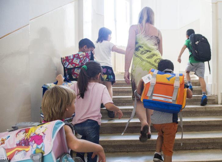 Diákok sétálnak fel a lépcsőn a Katolikus Karitásztól ajándékba kapott iskolatáskákkal hátukon a VIII. kerületi Németh László Általános Iskolában 2015. szeptember 2-án