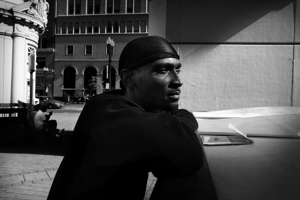 """Shanon Fulcher, azaz """"Bam"""" az oaklandi városháza előtti téren, 2012 szeptemberében. Los Angelesben nőtt fel, és már nagyon fiatalon a hírhedt Bloods tagja lett (a két legprominensebb fekete bűnbanda egyike, a másik a Crips). Hatszor állt bíróság előtt, kétszer kábítószerbirtoklás, négyszer illegális fegyverviselés miatt - mind a hatszor el is ítélték. Miután több barátját is elvesztette a bandaháborúkban, Oaklandbe költözött, hogy a rokonainál húzza meg magát."""