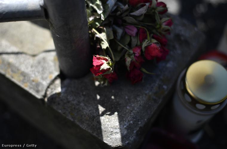 A pár áldozataira emlékező virágok és gyertyák a lezárt házat körülvevő kerítés lábánál