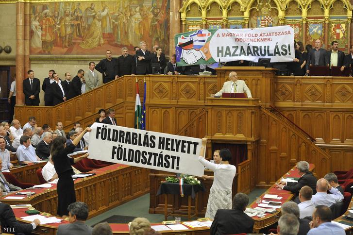 Szél Bernadett és Osztolykán Ágnes független képviselők (LMP) a patkóban az Országgyűlés plenáris ülésén 2013. június 21-én. A Jobbik-frakció tagjai az elnöki emelvényentiltakoztak a földtörvény ellen.