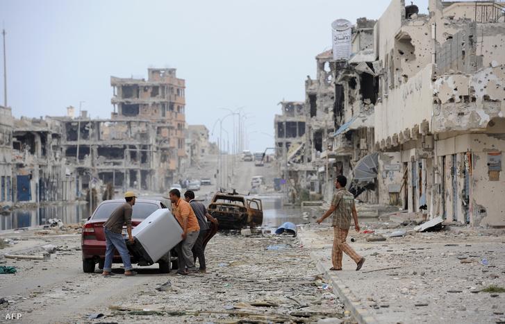 Egy bombatámadás utáni romok között a líbiai lakosok Szirtében.