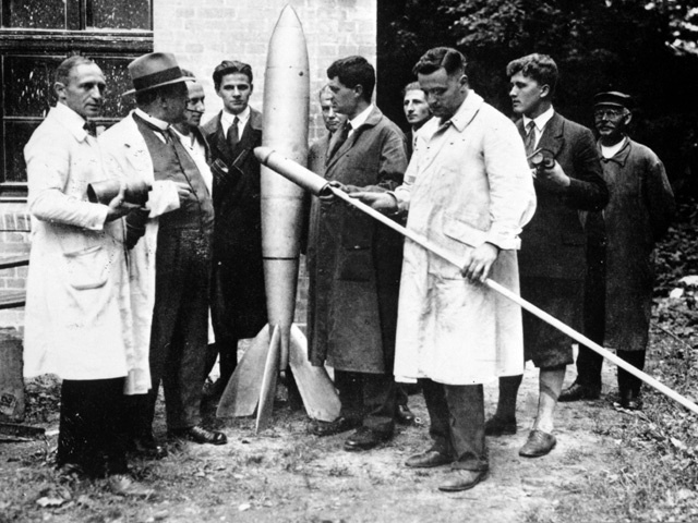 Az őrült rakétások (VfR) tagjai. Rudolph Nebel a bal oldalon, Hermann Oberth, az első elnök a rakétától jobbra, Klaus Riedel, kezében a kis rakétával és mögötte a fiatal Wernher von Braun.