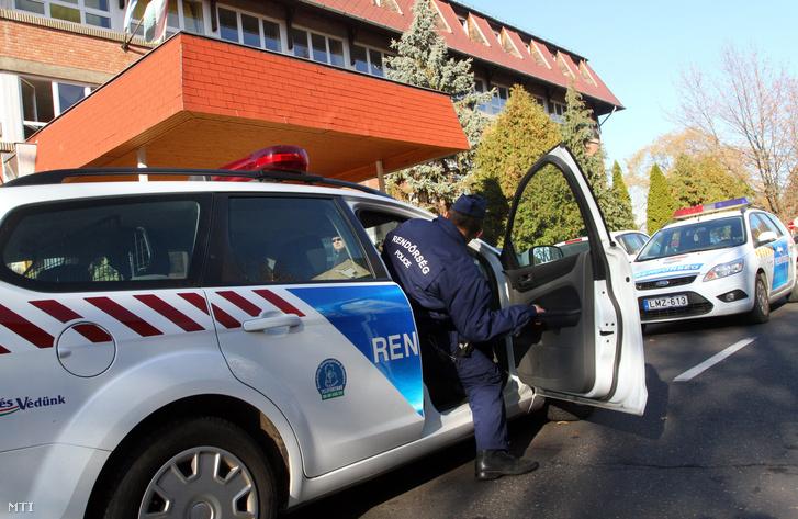 Rendőrök érkeznek a tiszaújvárosi Eötvös József Gimnázium Szakképző Iskola és Kollégium épületéhez, ahol korábban egy fiú megszúrta két társát,2011. november 16-án.