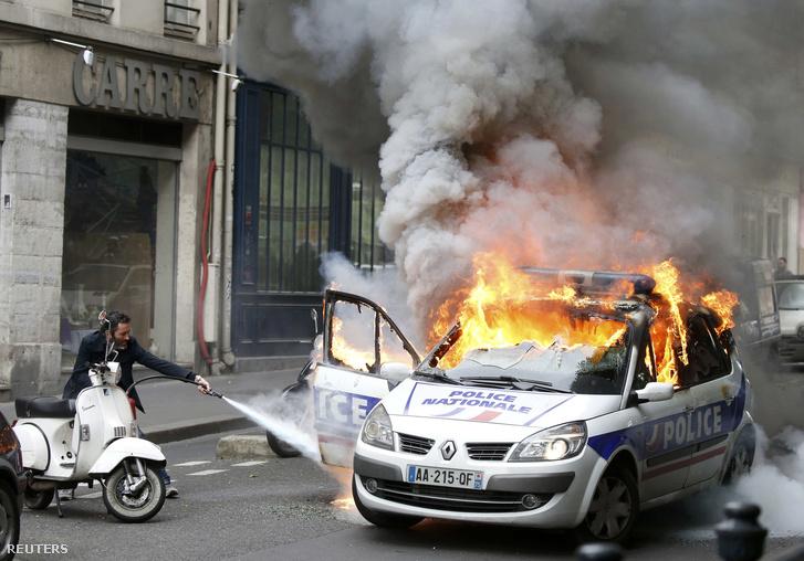 Égő rendőrautó Párizsban a francia rendőrség tüntetésén, 2016. május 18-án. A francia rendőrök a munkajogi reform elleni, erőszakos cselekményekbe hajló tüntetéseket kívánta elítélni a megmozdulással, de ellentüntetők támadták rájuk és kezdek gyújtogatásba.