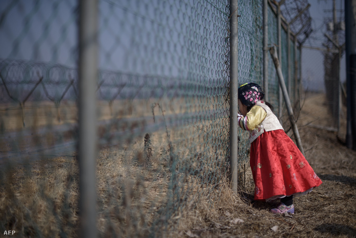 Egy hagyományőrző ruhában lévő lány néz át a katonai kerítésen Észak-Koreában.