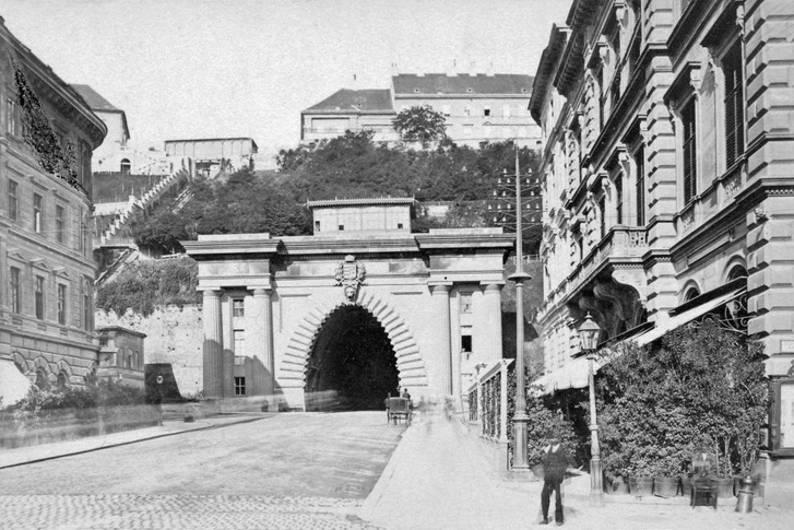A mai Clark Ádám, az egykori Lánchíd tér 1900-ban. Jobb oldalon, a mai foghíj telek helyén a Budai Takarékpénztár, aljában a kávéház dézsás növényekkel zöldített terasza