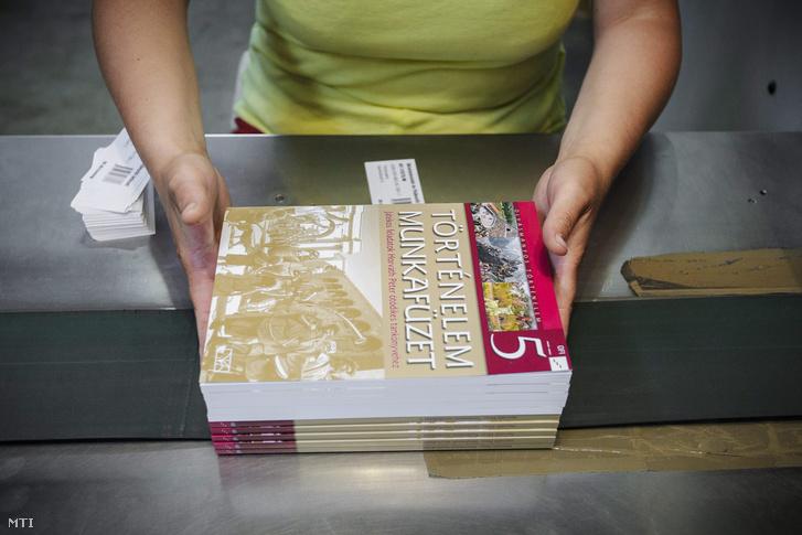 Történelem tankönyveket pakol egy dolgozó a debreceni Alföldi Nyomdában 2015. május 13-án.