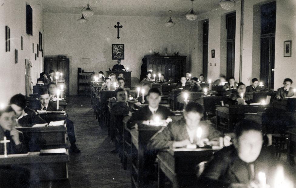 """A pécsi Pius Gimnázium diákjai gyertyafény mellett tanulnak. 1936-ban járunk. Az internátusban a diákok életkor szerint szakaszokba voltak osztva, ezeket egy még pappá nem szentelt  rendtag, ún. magiszter vezette, aki – a gimnáziumi foglalkozás kivételével – minden idejét a szakaszával töltötte. Ő felügyelt a kötelező tanulóidők alatt, szervezte a programokat, """"lelki olvasásokat"""" tartott, sőt még egy hálóteremben is aludt a gyerekekkel."""