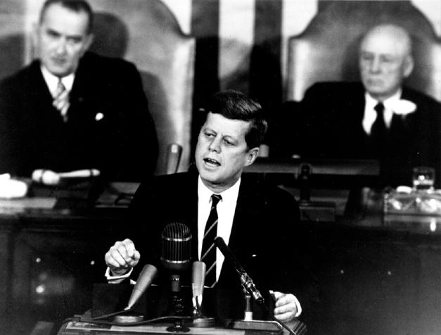 """1961. május 25-i kongresszusi beszédében John F. Kennedy amerikai elnök megígérte, hogy az Egyesült Államok még az évtized végéig embert juttat a Holdra, és az asztronautát """"onnan biztonságban vissza is hozza""""."""