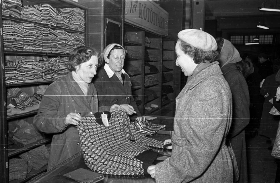 Női kötöttáru kis változatosággal, de a dolgozói igényeket biztosító mennyiséggel 1956 végén. Fél évvel a forradalom eltiprása után, 1957 májusában a korai Kádár-rendszer nagy sikereként több százezres nagygyűléssel tudták demonstrálni a hatalom megszilárdítását. Ekkor már teljes fordulatszámon pörgött a megtorlás, Kádár túl volt a moszkvai jóváhagyáson, hogy Nagy Imrét bíróság elé állítják, akit aztán április közepén le is tartóztattak a társaival együtt. A miniszterelnök kivégzéséig még hátra volt egy bő év volt, de a fontos dolgok ekkor már eldőltek pár évtizedre.
