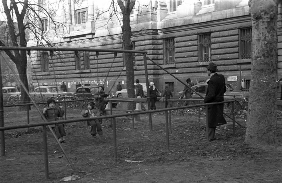 """""""Munkával harcolj a jövőnkért""""; """"Béke, függetlenség, jólét!"""" - áll a Magyar Nemzeti Bank falán a rendszerhű késő-56-os graffiti. A hintákban hintáznak, a dolgok lassan visszatérnek a rendes kerékvágásba, arról meg itt nincs szó, hogy a kádári szótár nemsokára kissé átalakul, és a szovjet csapatok tartós maradásával a függetlenséget olyan nagyon már nem fogják hangsúlyozni."""