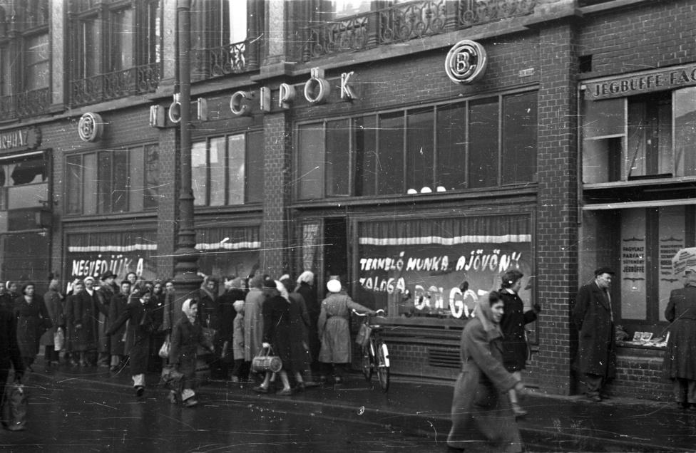 """""""Termelő munka a jövőnk záloga. Dolgozz!"""" - hirdeti a Felszabadulás (előtte és utána Ferenciek) teri Jégbüfé melletti cipőbolt kirakata. A sor nem rövid, talán nem is lábbeliért állnak, de ha a kép újságban is megjelent, akkor a fő üzenet úgyis az volt, hogy emberek, a boltok nyitva vannak, a dolgozók megvédik a szocialista fejlődés eredményeit."""