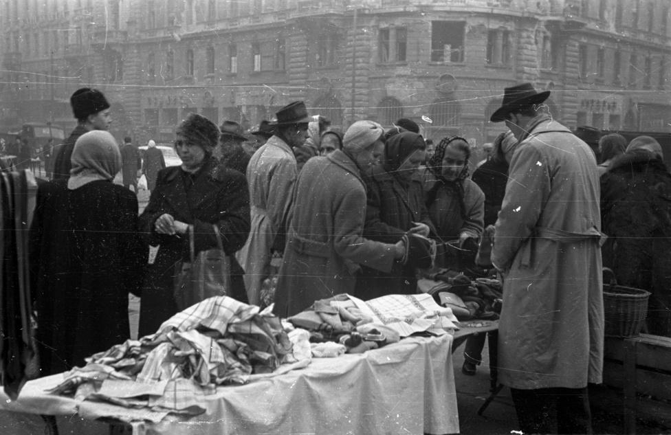 Bauer itt látható képei közül több az ellátás biztosítását mutatja: ételosztás teherautóról, válogatás utcai standnál, az árusítás újraindulása a belvárosi boltokban. Hogy ez szándékos, az anyagi konszolidációt sugalló propaganda szolgálatában álló témaválasztás, vagy esetleg csak a puszta dokumentáció volt a fotóriporter szándéka, legfeljebb csak találgatható - mindenesetre érdekes, hogy a Kádár-rendszer legitimációjában később évtizedeken át meghatározó fogyasztói szocializmus-ábrázolásoknak már ezekből a hetekből is maradtak fenn előképei.