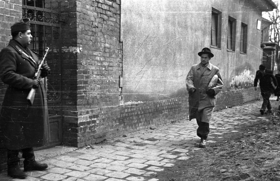 Archetipikusnak ható XX. századi magyar életkép géppisztolyos katonával, a hóna alatt kenyeret cipelő kalapossal és meggörnyedt férfival.