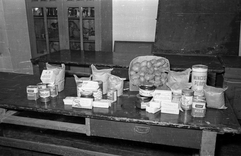 Nyugati segélyszállítmány kicsit kirakatszerűen elrendezve, a bútorzat és a szekrény tartalma alapján egy átmenetileg új funkciót kapó iskolai biológiaszertárban járhatunk. Az asztalon hús- és tejkonzervek, levessűrítmény, margarin és a magyar családoknak szokatlan furcsaság: pálmazsír.
