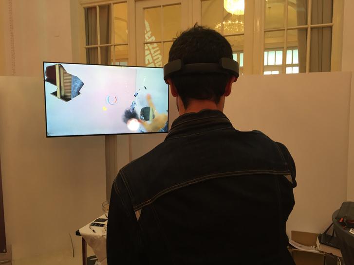 A Hololens foltokban rajzolja fel a virtuális objektumokat a helyükre, nincs hagyományos tévézős érzésünk, hogy egy téglalapot nézünk. A demó külső szemlélését segíti tévé bal felső sarkában látható, hogy sikerült átlőnöm a falat.
