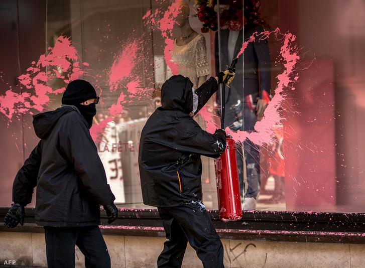 Tüntetők fújnak le festékkel egy üzletet Lillében 2016. április 28-án.