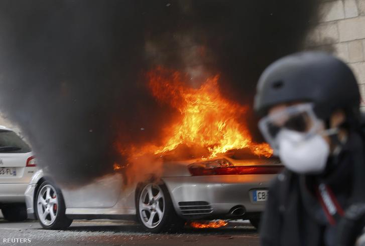 Egy fotós menekül Nantesban, miután a tüntetők felgyújtottak egy autót, 2016. április 28-án.