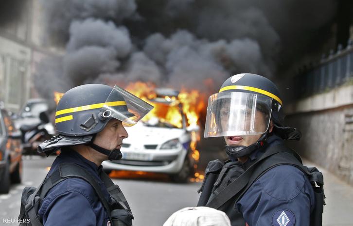 Rendőrök egy égő autó előtt Párizsban, 2016. május 18-án
