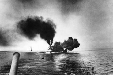 Sűrű füst a német SMS Schleswig-Holstein körül.  A hajó túlélte az első világháborút, annyira, hogy 1939. szeptember elsején hajnalban erről adták le az első lövéseket a lengyel Gdańsk kikötője ellen. Az oktatóhajóvá átalakított járművet 1944-ben brit bombázók intézték el, a háború után a szovjet haditengerészet használta partra vontatott célpontként. Bizonyos részei ma is megtekinthetők a drezdai hadtörténeti múzeumban.