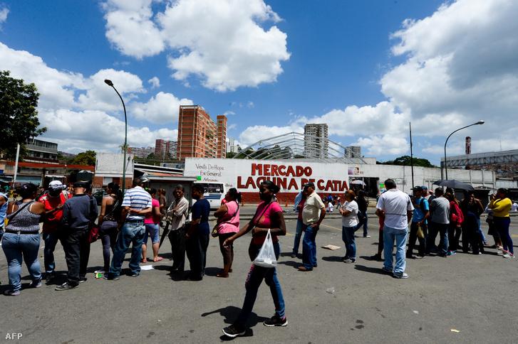 Hosszan kígyózó sor egy élelmiszerbolt előtt Caracasban