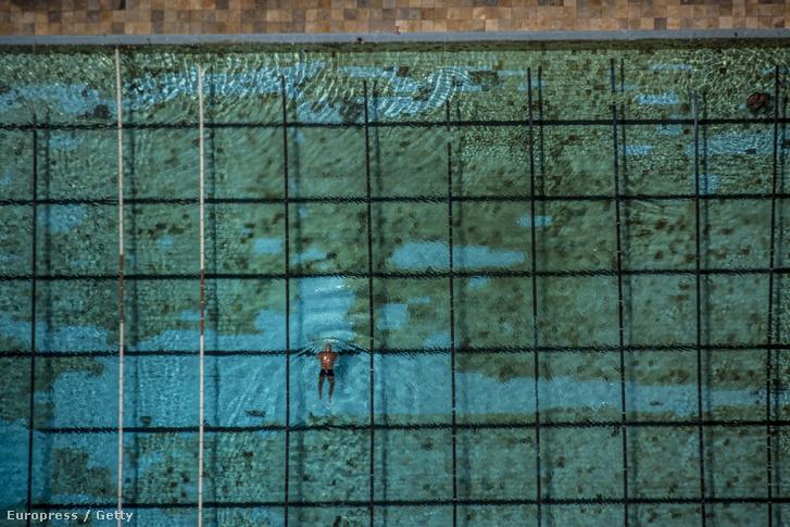 Gyengén karbantartott medencében úszik egy brazil férfi az olimpiai park szomszédságában.