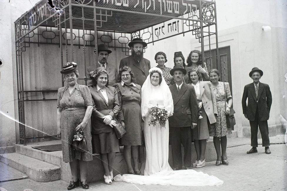 """Ennél is életbevágóbb volt a ruha kérdése a menyasszonyoknál. Egy ostromot csodával határos módon átvészelt esküvői ruha, fátyol és fejdísz ára az aranyéval vetekedett. Esetleg """"közel-ellős ötéves tehenet"""" ért, egy 1946-os apróhirdetés szerint. Szóba jöhetett még Joint- vagy más külföldi csomagban kapott ruha, kölcsönzött ruha, esetleg cserélt ruha."""