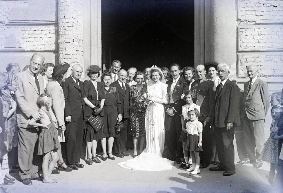 Egy tökéletes példa a korszak kettősségére: a pár és a násznép elegáns ruháját ellensúlyozza a romos templombejárat és a mezítlábas, otthonkás bámészkodók és utcagyerekek.