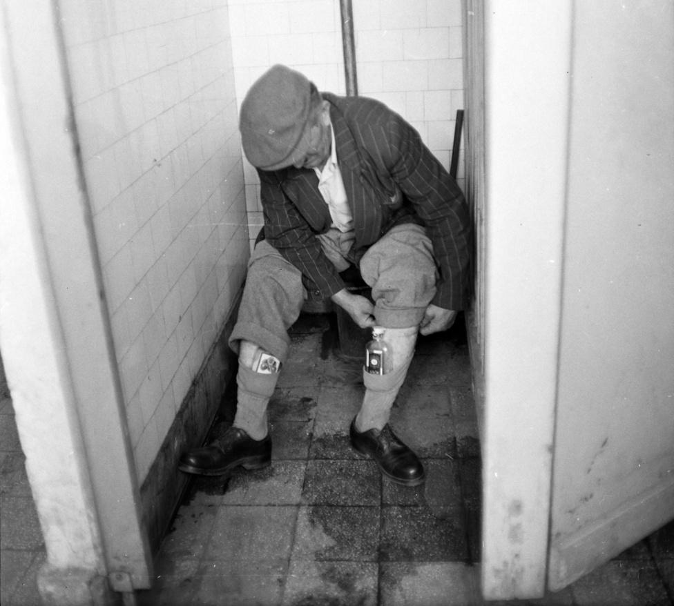 Az egyik zokniban tán szilva, a másikban barack. Pálinka. A vécén csücsülő úr talán egy fülön csípett szeszcsempész.