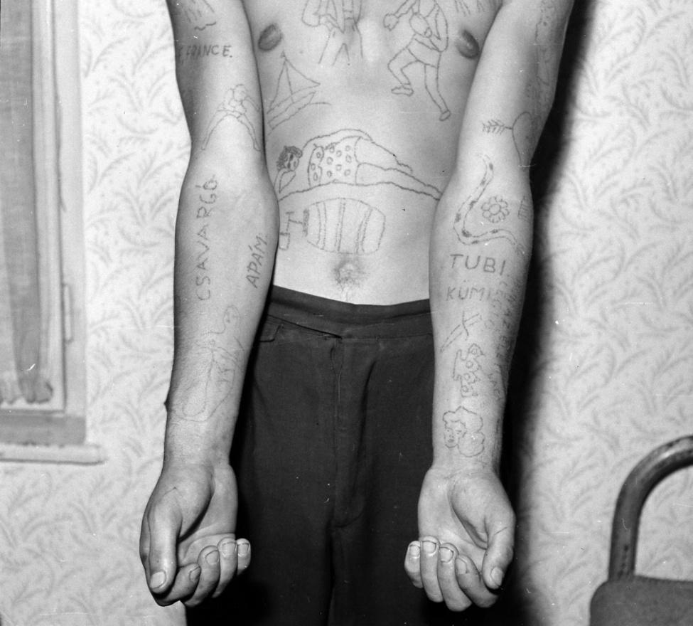 Csavargó, apám, France, Tubi, Kümi. Miért tetováltat valaki ilyen szavakat a testére? A dekorációból nem hiányzik a sellőlány, a kígyó, a bokszoló, a fürdőző matróna. A koszos körmű férfi mintha csak bilincselésre várna.