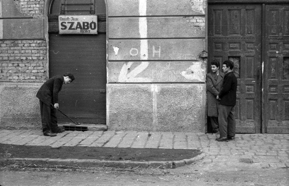 Rejtély a szabómesternél. Helyszínelők, nyomozók és bámészkodók Németh Imre szabómesternél, akinél le van húzva a roló. Valószínűleg az utcán történt valami, aminek akár köze sincs a szabómesterhez. De ki ez a titokzatos szabó? Ugyanilyen nevű szabó dolgozott 1943-ban a Vörösmarty utca 2-ben, de nem tudható biztosan, hogy most nála járunk. Az OH jelzés a falon a fehér nyíllal egy II. világháborús óvóhelyet jelez. Ezt talán használták 1956-ban is.