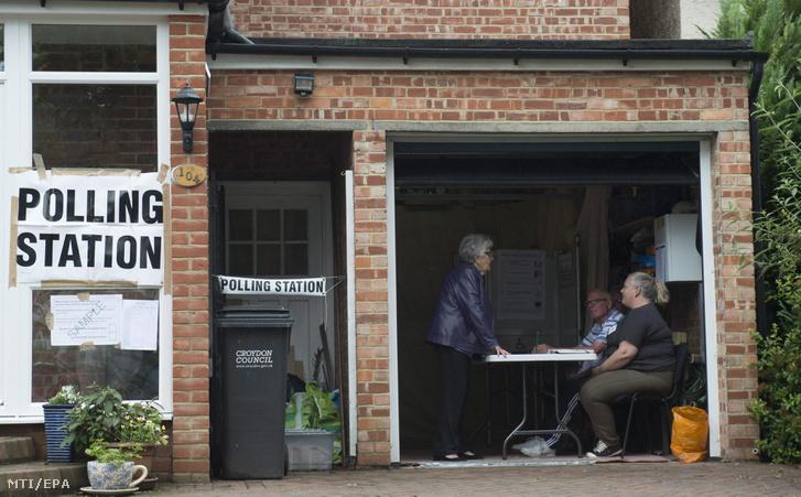 A választási bizottság tagjai egy privát ház garázsból kialakított szavazóhelyiségben, London déli kerületében, Croydonban