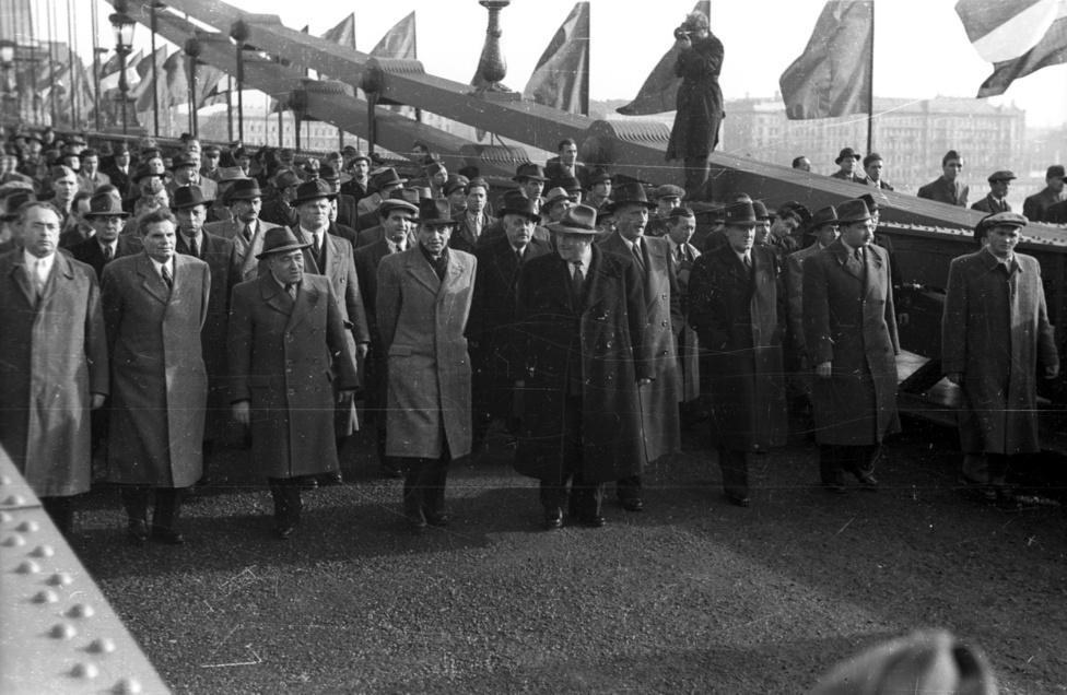 Nagyot ugrunk az időben, a rendszer változik, a jellege nem. 1949-ben vagyunk, méghozzá a Lánchídon, az újjáépített híd átadási ünnepségén. A menet élén ott van Dobi István miniszterelnök, későbbi minisztertanácsi elnök, majd az Elnöki Tanács elnöke (államfő), de ott vonul Rákosi Mátyás, Gerő Ernő és, cigarettával Kádár János is. Nem a hagyományos értelemben vett tömegrendezvény ez, a politikai elit is az utcára (a hídra) vonul, a fotóról az sajnos ki sem derül, mennyi embert és mennyire közel engedtek ezekhez az Ócseny Vázsnij Cselovekokhoz, sőt, Továrisokhoz.