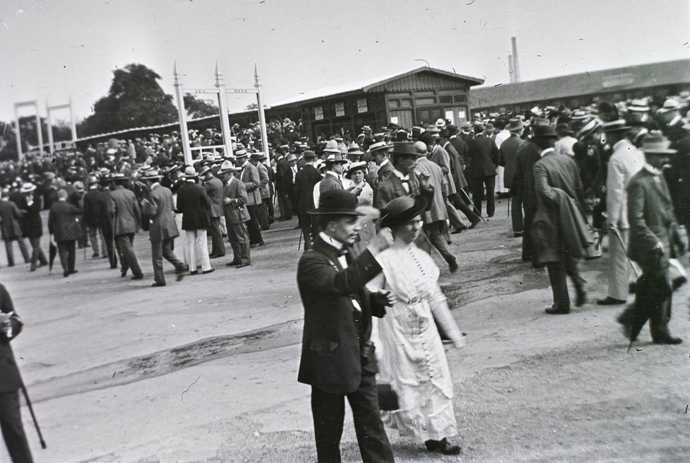 Jól öltözött hölgyek és decens urak korzóznak a későbbi Népstadion helyén lévő városligeti Lóversenytéren ezen az 1912-ben készült felvételen. Zsakettek, kalapok, sétapálcák árulkodnak a békeévek nyugalmáról. Azonban nemzetközi helyzet már fokozódik, és nem csak az: a társadalomban is egyre erősödik az elégedetlenség.