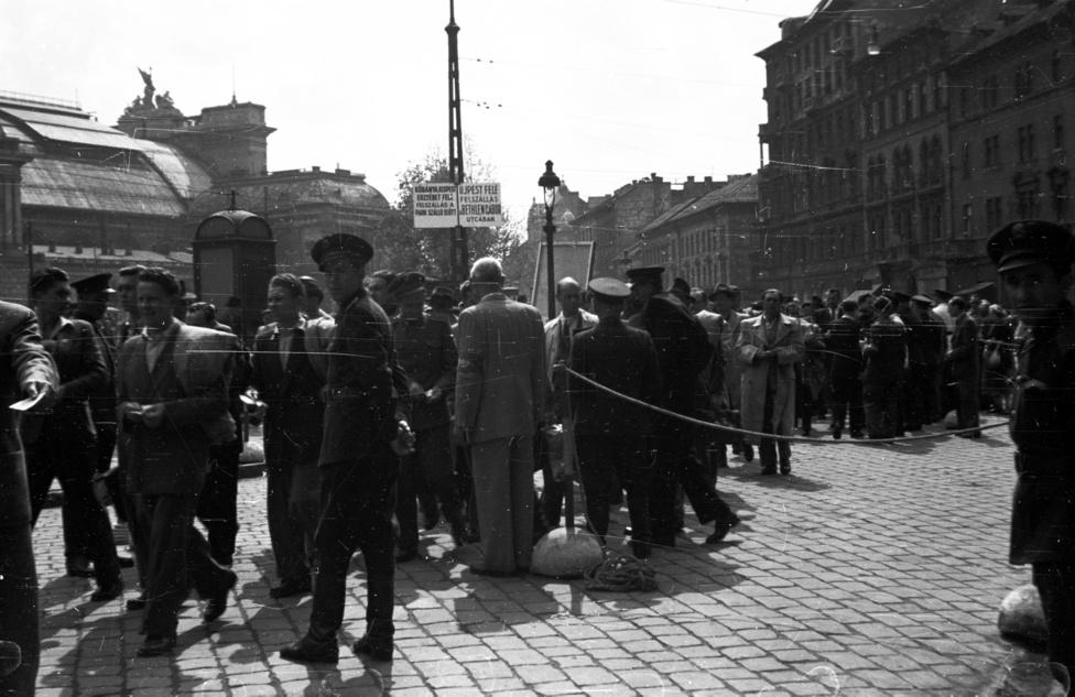 Utcai forgatag a Baross tér a Verseny utca torkolatánál 1953-ban – ennyit tudunk a fotóról. A képen a korszellemhez képest is nagy számban szerepelnek rendőrök, amiből arra gondolunk, hogy ez nemcsak egy átlagos szombat délután, amikor mindenki a Keleti felé iparkodik, hogy a hatnapos munkahetet kipihenje, hanem valamilyen rendezvényre tódul a tömeg. És hogy hová? A helyszínből arra tippelünk, hogy a Népstadion átadására, az ugyanis épp ebben az évben volt: 1953. augusztus 20-án.