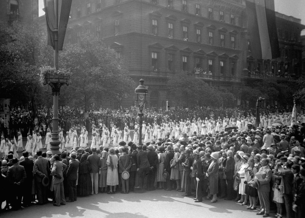 Szintén 1938, szintén Szent István ünnepe, de már az Andrássy út, ahol a Szent Jobb-bal folyik az ünnepi felvonulás. Militáns hangulatnak itt nyoma sincs, de a felvonulók egyenruhája és az, hogy az ünneplők csak az úttest két oldaláról nézhetik a menetet, ugyanazt jelzi, amit az előbb említettünk: a tömeg akkor jó, ha vezényelten vonul és szépen, rendezetten áll. Elvileg ünnepség van, de felszabadultságnak, boldogságnak a katonák hiánya ellenére sincs nyoma a képen.