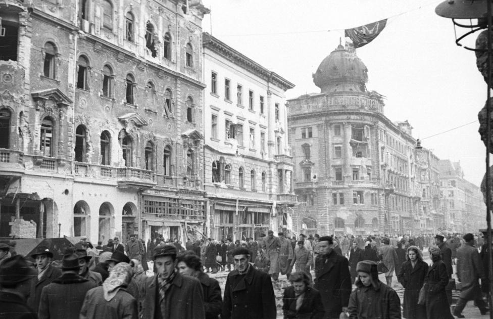 Tömeg az utcán úgy, ahogy azt a hatalom, a politika legkevésbé szereti: spontán és elégedetlen tömeg. 1956-ban vagyunk, ez a Rákóczi út az Akácfa utca felől, a Baross tér felé nézve (középen a nagykörúti kereszteződés). Míg az 1989-90-es rendszerváltozást a Kádár-rendszerrel elégedetlen elit indította el és vitte sikerre érdemi utcai tömegmegmozdulások nélkül – nem úgy, mint például a lengyeleknél, románoknál –, addig 1956 az utca forradalma, az elégedetlen tömegek forradalma volt, spontán és önszerveződő.