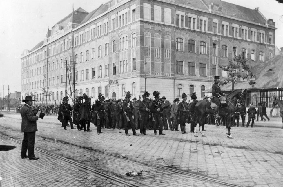 Hogy mennyire, azt jól jelzik a tragikus vérvörös csütörtök eseményei. Az előző fotóhoz hasonlóan ez a kép is 1912-ben készült, ennek a pontos dátumát is tudjuk: május 23-án. Aznap, amikor százezres tömeg gyűlt össze az első világháború előtti legnagyobb tüntetésen. Az összeverődött, általános választójogot és Tisza István távozását követelő tömeget rendőrök, csendőrök és katonák brutális akciójával oszlatták szét: a békés tüntetők közül hatan meghaltak, és több száz sérültje is volt a fegyveres beavatkozásnak. A fotó a mai XIII. kerületben készült, a Váci út és a Janicsár utca sarkán – a háttérben lévő épület elemi iskola volt, ma is iskolaként működik, mögötte áll ma a József Attila Színház –, egy olyan városrészben, ahol már akkor komoly bázisa volt a munkásmozgalomnak és a baloldali (szociáldemokrata) ideológiának. A képen még viszonylagos béke van a tüntetők és az egyenruhások között.