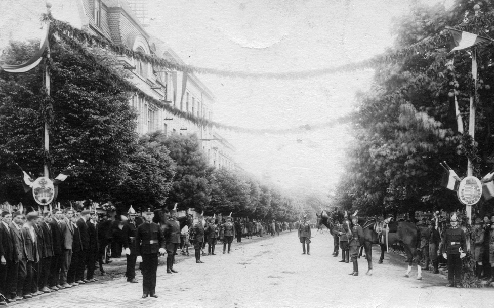 A fotó a Baross utat mutatja a Kossuth Lajos utca felé nézve. A tömeg Horthy Miklós érkezését várja 1927 májusban. Hol van ekkor már a fehérlovas bevonulás a bűnös városba! A székesfőváros pompás ünnepségen köszönti a kormányzót – a látványos, ünnepi hangulatú tömegrendezvények nagy gyengéi voltak a magyar politikai rezsimeknek. Fontos volt az előre kidolgozott koreográfia éppúgy, mint a leglelkesebb és legmegbízhatóbb hívek mozgósítása – bár akkor, egy évvel a koronát váltó stabil pénz, a pengő bevezetése után, a bethleni konszolidációban nyakig benne elég könnyű is lehetett őszintén lelkes polgárokat találni.