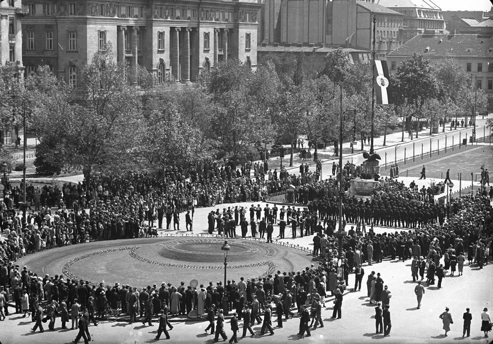 1940 van, Európa már háborúban, a budapesti Szabadság téren Irredenta emlékhely létesül, a kép az országzászló felhúzásának pillanatában készül. Ünnepség ez is, de itt még kevesebb a pátosz, a pozitív érzelmek meg pláne: a fotó egészében van valami nyomasztó, érződik rajta a közelgő véres évek előszele.