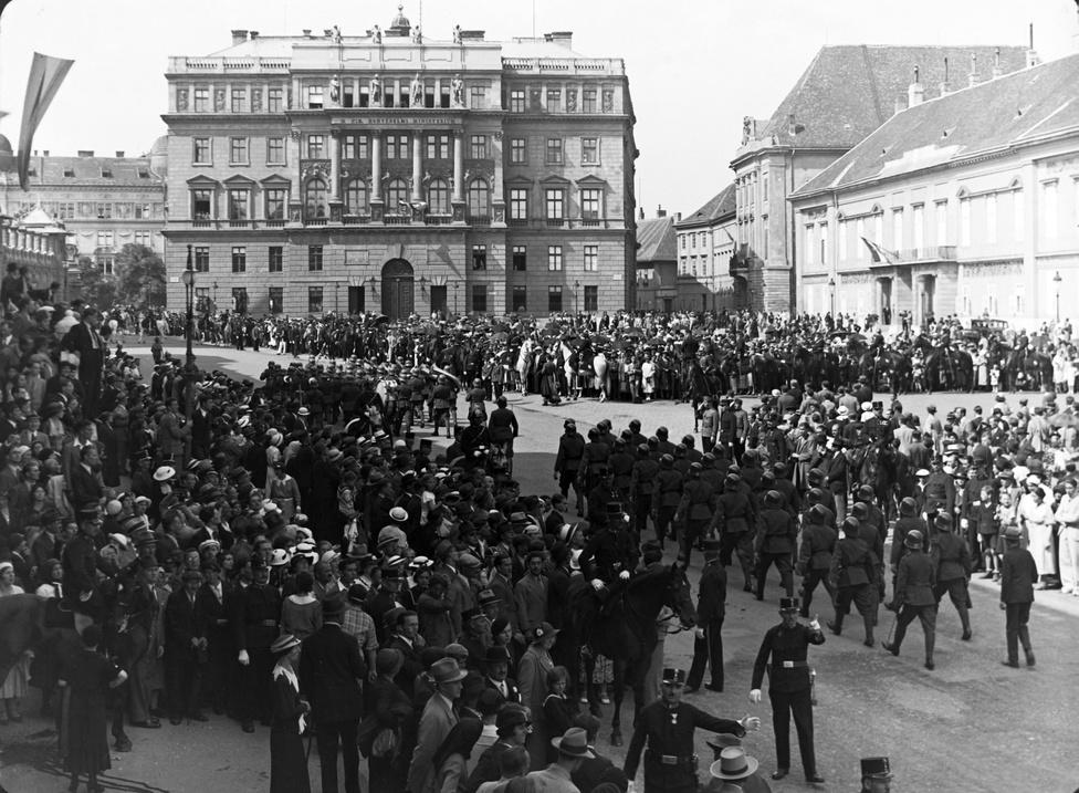 Ha rövid a kardod, told meg egy ünnepléssel – így lehetne kicsit kifordítani az ismert mondást. 1938-ban vagyunk, augusztus van, Szent István napi ünnep a Szent György tér, szemben a Honvédelmi Minisztériummal. Csaknem fél évvel vagyunk azután, hogy Darányi Kálmán meghirdette az egymilliárd pengős hadsereg-fejlesztést, a győri programot, de még csak ezután (novemberben) jön az első bécsi döntés. Európa háború felé tart – bár ekkor még aligha sejti bárki is, milyen véres és kegyetlen háború felé –, az ünnepségen felvonuló katonák nem díszmentés huszárok, hanem páncélsisakos bakák. És közben az ünnepség részeiként egyszerre szimbolizálják, milyennek szereti látni a hatalom az utcán vonulókat: rendezettnek, szervezettnek, jól irányíthatónak – sőt, irányítottnak.