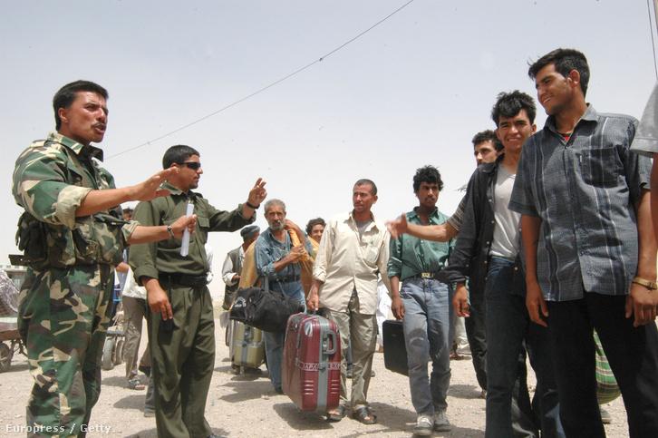 Afgán menekülteket terelnek iráni katonák egy ellenőrzőpontnál.