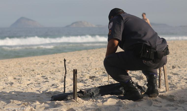Egy rendőr guggol az egyik nejlonzsákba csomagolt emberi testrész mellett