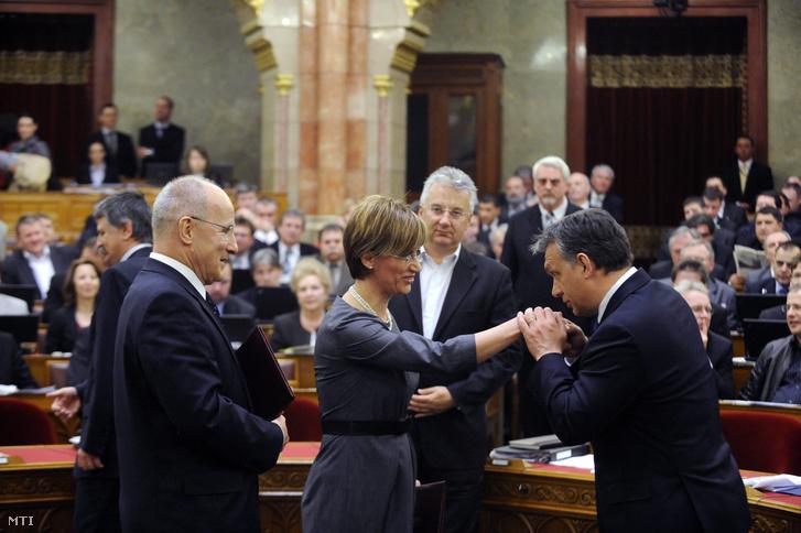 Orbán Viktor miniszterelnök kézcsókkal gratulál Bártfai-Mager Andreának a Magyar Nemzeti Bank monetáris tanácsa új tagjának akit az Országgyûlés 292 igen szavazattal 37 ellenében választott meg. Balra áll Gerhardt Ferenc a tanács másik új tagja akit az Országgyûlés 300 igen szavazattal 40 nem ellenében választott meg. (2011.)