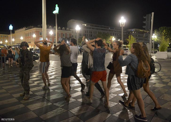 Az ünnepről hazafelé tartók feltartott kezekkel haladtak el a rendőrök mellett.