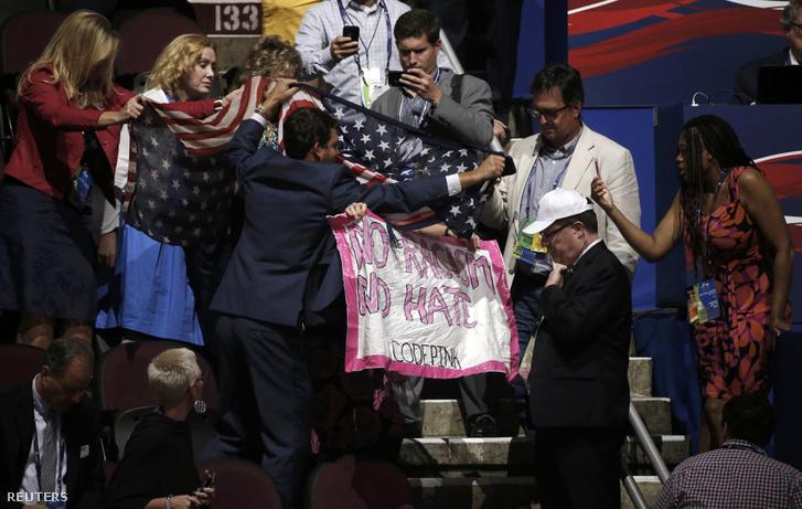 A közönség soraiban valaki szót emelt Trump gyűlöletkampánya ellen, a képen az elnökjelölt támogatói tépik ki a kezéből a zászlót.