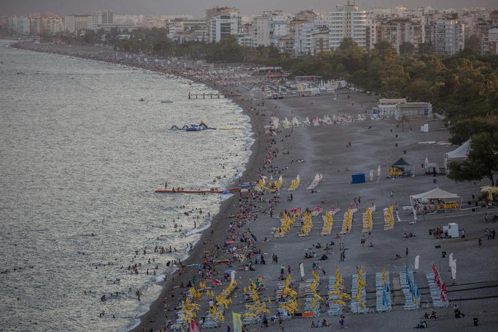 Turisták a naplementében a török tengerparton