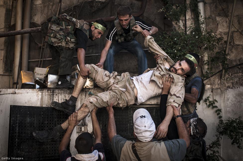A szíriai tűzharcok eleinte elszigetelt összetűzések voltak: az ország területének legnagyobb részén nem volt fegyveres harc az SZSZH és a szír hadsereg erői között. 2012 januárjára viszont a konfliktus polgárháborúvá változott. Ekkor még a Szabad Szíriai Hadseregnek alig voltak páncélozott járművei. Pusztán rajtaütéseket hajtottak végre, melyet egy törökországi támaszpontról szervezett meg a 60-70 fős katonai tanács. A képen látható harcos Aleppóban sérült meg 2012. augusztus 20-án, miután társaival megpróbáltak kiiktatni egy mesterlövészt a városban, amely beszorította a Szíriai Szabad Hadsereg csapatait.